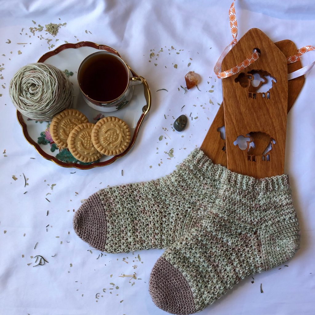 toe up crochet socks in sock blocker. flat lay with a plate of tea and cookies.