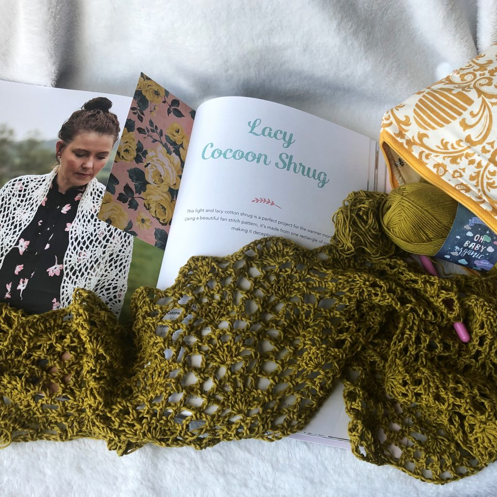 romantic crochet book open to the Lacy Cocoon Shrug page. Displayed with the start of said pattern with an olive colored yarn.