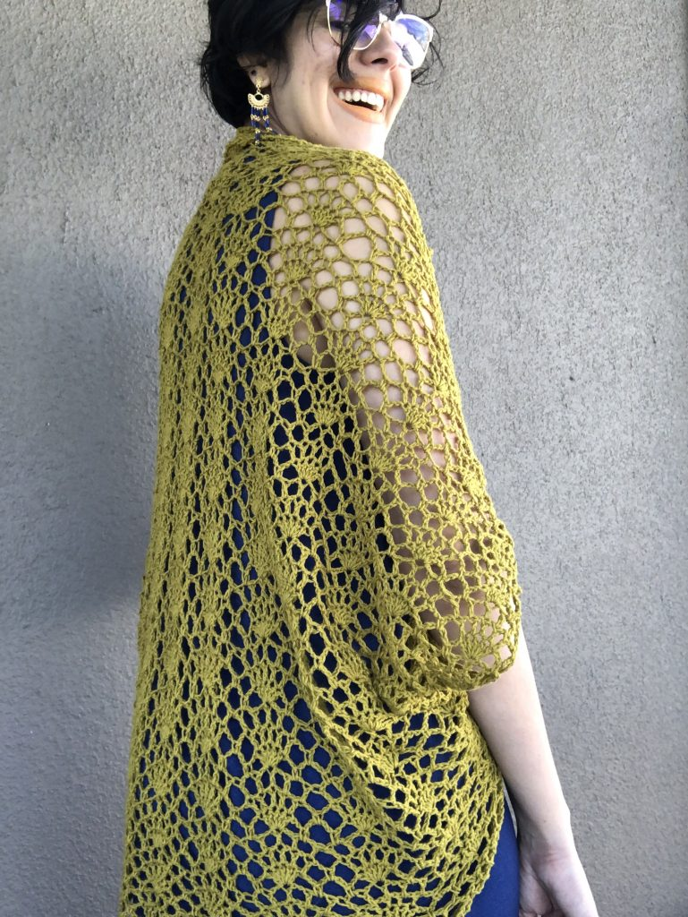 Clarisa wearing the finished lacy cocoon shrug over a blue sleeveless dress. Pattern from the romantic crochet book.