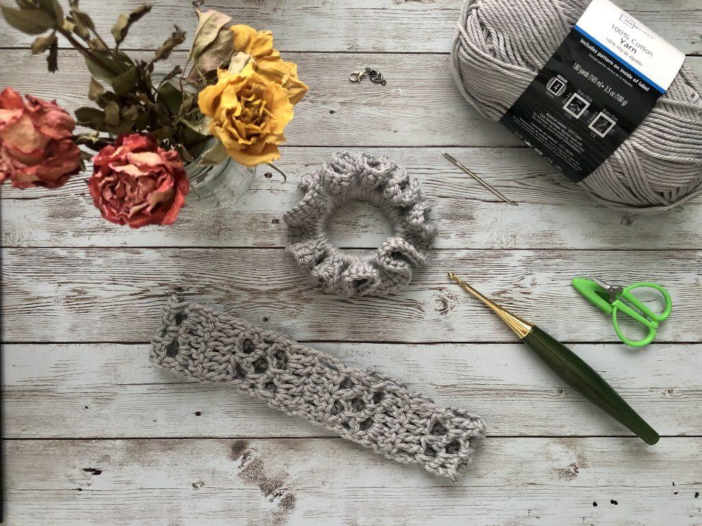 crochet keyhole headband in silvery grey yarn with some flowers.