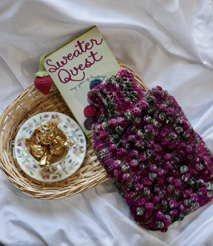 hot water bottle cozy complete shown here on a basket with a book and some chocolates