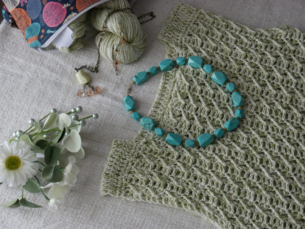 summer vest. A flat lay featuring the summer breeze top paired with a flintstone type turquoise necklace.