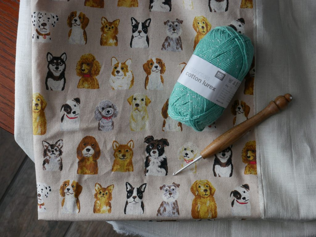 turquoise yarn and crochet hook laying atop handmade tablecloth sewn with kokka dog breed fabric