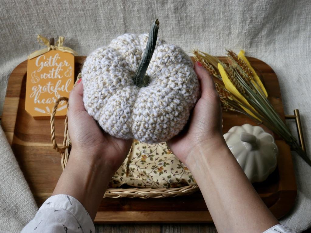 holding a white crochet pumpkin