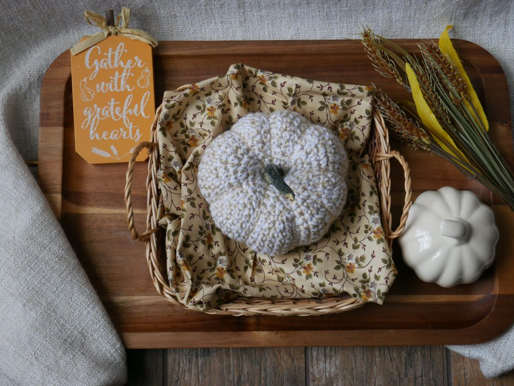 white crochet pumpkin displayed with a cream ceramic one, plastic wheat and a autumn sign.
